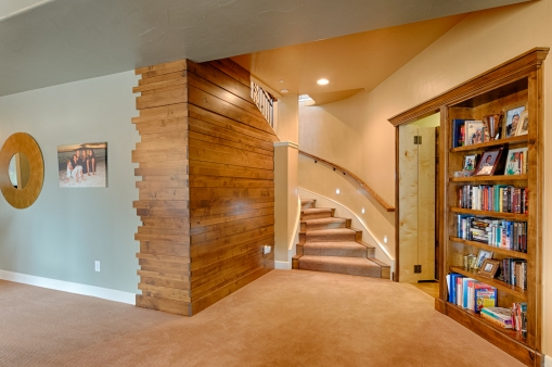 Basement Stairwell with Wood Wall Detail and Bookshelf Reveal